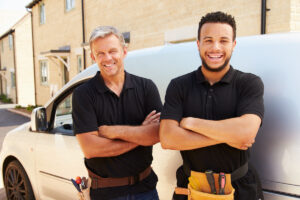 picture of happy plumbers by their fleet vehicle